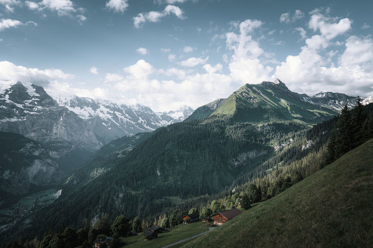 Scenic view of cabins and mountains against sky