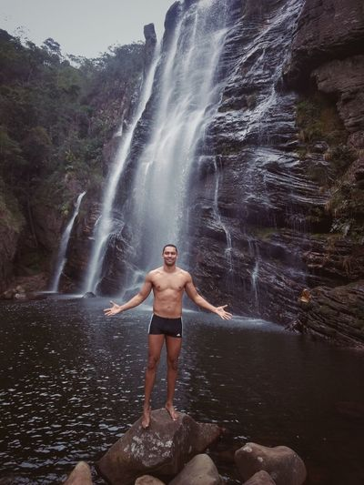 Full length of shirtless man standing against waterfall