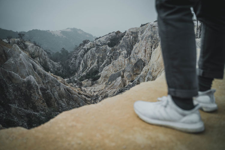 Low Section Human Leg Mountain One Person Body Part Real People Shoe Human Body Part Lifestyles Leisure Activity Standing Rock Scenics - Nature Day Nature Human Foot Mountain Range Rock - Object Solid Outdoors Jeans Human Limb