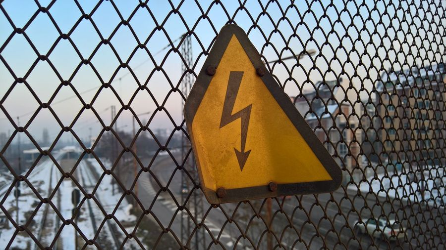 Close-up of yellow high voltage sign on chainlink fence