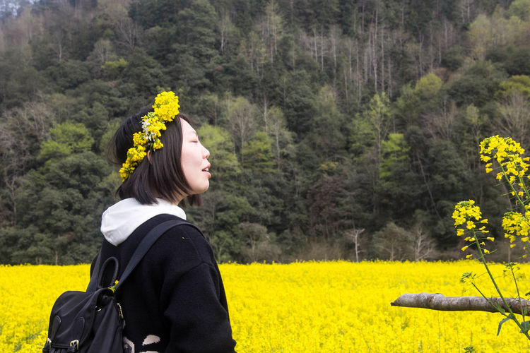 Woman with yellow flower crown in field