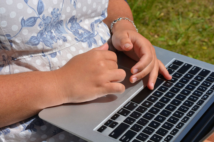 Teenager using a laptop outdoors Close-up Communication Computer Connection Day Human Body Part Human Hands Keyboard Laptop Outdoors Portable Information Device Real Person Studying Technology Teenager Track Pad Wireless Technology Woman Women Only