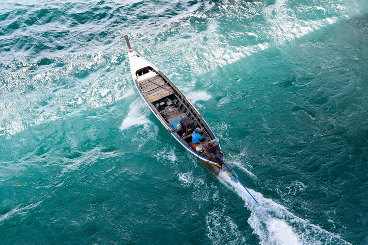 High angle view of man sitting in motor boat on sea