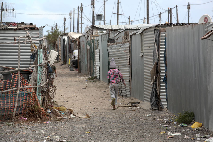 Child running through the streets of Blikkiesdorp, a township in South Africa Architecture Blikkiesdorp Building Exterior Built Structure Day Full Length Grey Sky Hut One Person Outdoors People Poverty Real People Running Sky Tin Township