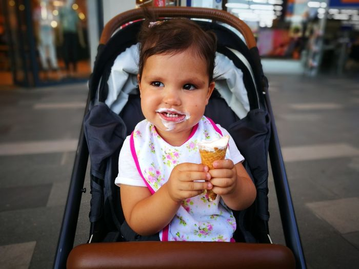 Cute girl eating ice cream while sitting in baby carriage