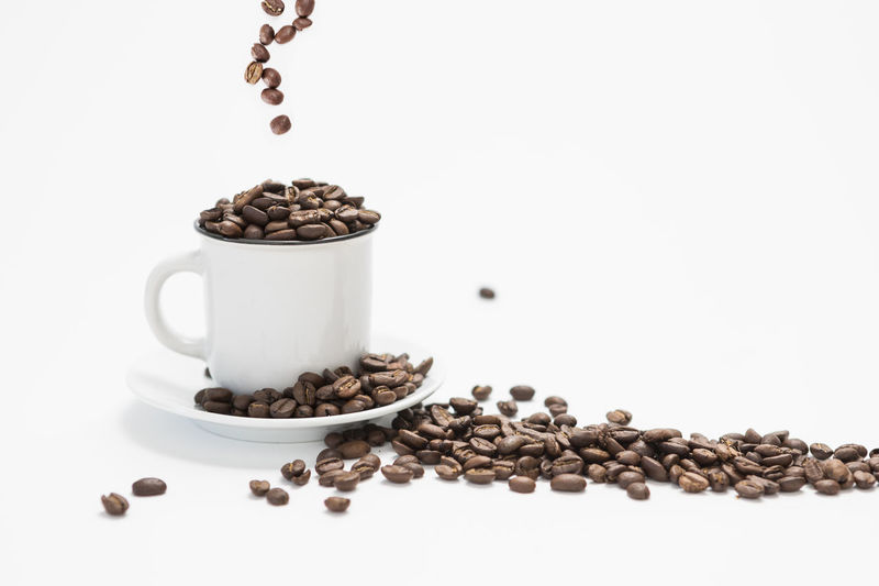 White Coffee Cup With Fresh Coffee Beans Falling into the Cup on a White Background Concept with Copy Space Food And Drink Coffee - Drink Roasted Coffee Bean Coffee Still Life White Background Indoors  Food Studio Shot Freshness No People Brown Large Group Of Objects Coffee Bean Cup Roasted Refreshment Mug Drink Coffee Cup Caffeine Falling Water
