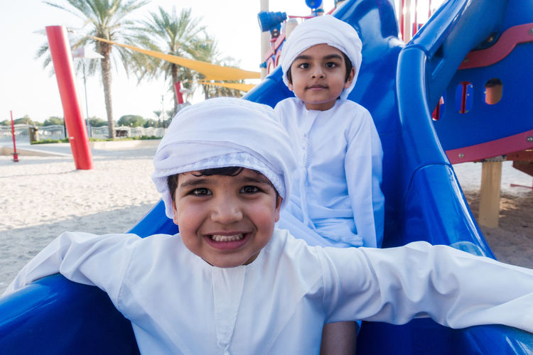 Portrait of smiling brothers wearing traditional clothing sliding in playground