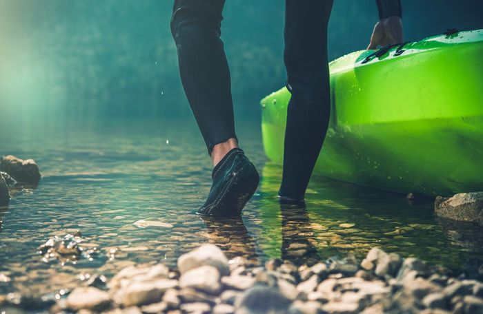 Kayaker Preparing For the Lake Trip. Closeup Photo Boat Kayak Kayaker Lake Recreation  Sportsman Summer Vacation Water