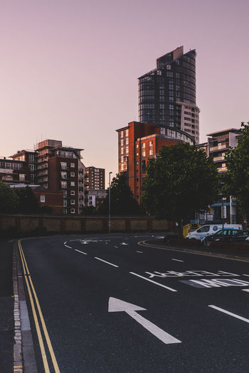 Diminishing Perspective Of Road By Buildings Against Clear Sky During Sunset