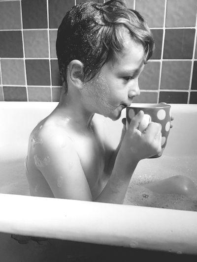 Shirtless Boy Having Coffee While Sitting In Bathtub