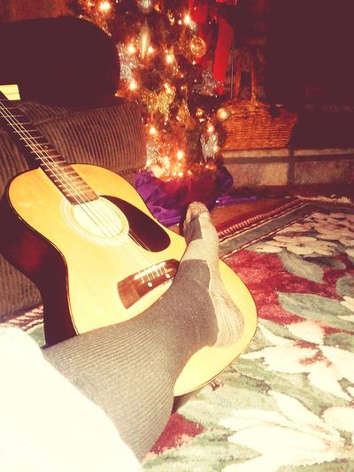 Country Christmas Musical Instrument Music Guitar Indoors  Adults Only Leisure Activity Lifestyles Plucking An Instrument Sitting Home Interior People Adult One Person Living Room Night Young Adult