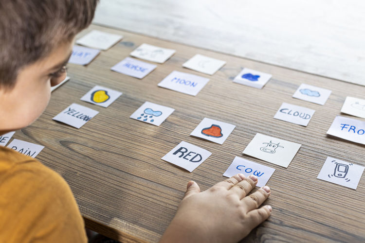 High angle view of boy holding text on table