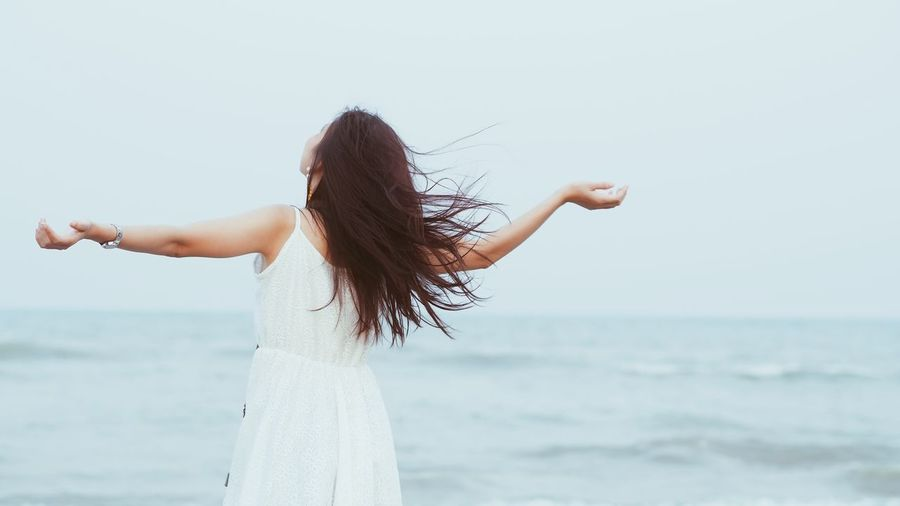 Rear View Of Woman Standing With Arms Outstretched By Sea Against Clear Sky