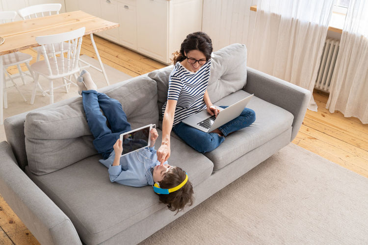 High angle view of man using mobile phone while sitting on sofa