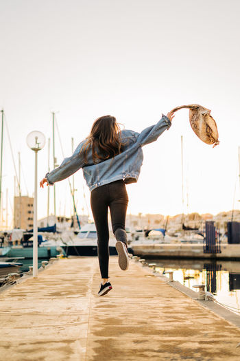 Rear view of young woman jumping at harbor during sunset