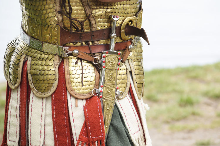 detail of an ancient roman soldier, legionnaire or centurion wearing a Lorica Squamata armor and a dagger at a historical festival, copy space Ancient Man Soldier Armored Centurion Close-up Dagger Day Festival Historical Legionnaire Lorica Squamata Metal Old Outdoors People Protection Roman Weapon