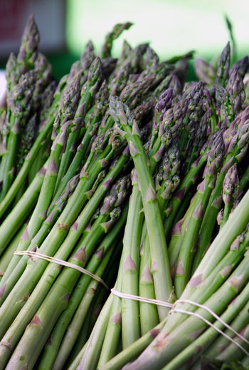 healthy eating with fresh, green bunches of asparagus at a local farmers market Farmers Market Freshness Green Abundance Asparagus Bunch Asperagus Bunch Close-up Food Food And Drink For Sale Freshness Green Color Healthy Eating Market Outdoors Raw Food Retail  Vegetable Veggie