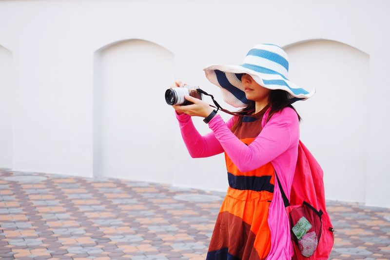 Thai girl in colorful cloths with wide hat in photography shooting action. EyeEm Selects Clothing One Person Real People Women Lifestyles Hat Side View Traditional Clothing Casual Clothing Standing Three Quarter Length Adult Young Women Wall - Building Feature Young Adult Scarf