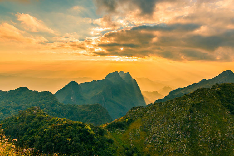 Beautiful scenic mountain background with blue sky, cloud and blast horizon sun