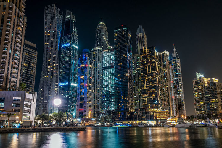 Illuminated modern buildings in city against sky at night