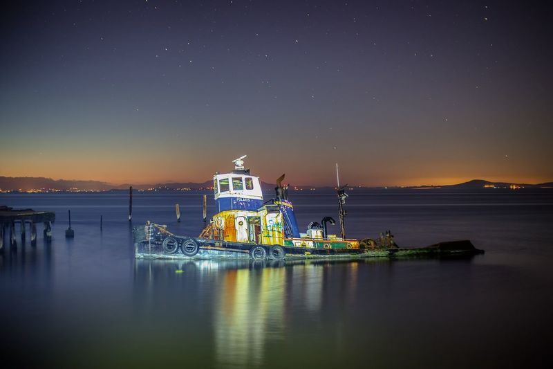 Tugboat On Calm Sea Against Sky At Dusk