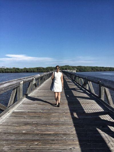 Rear View Full Length Of Woman Walking On Boardwalk Over Lake Against Blue Sky