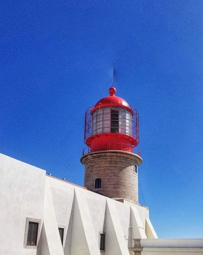 Low angle view of lighthouse against building against clear blue sky