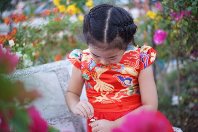 Girl holding flowers while sitting on bench by flowering plants