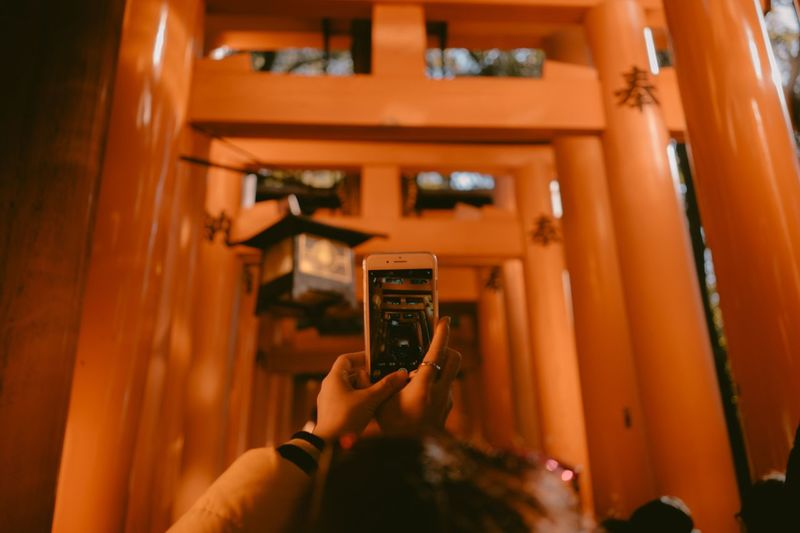 Close-Up Of Woman Photographing Torii Gate Through Mobile Phone