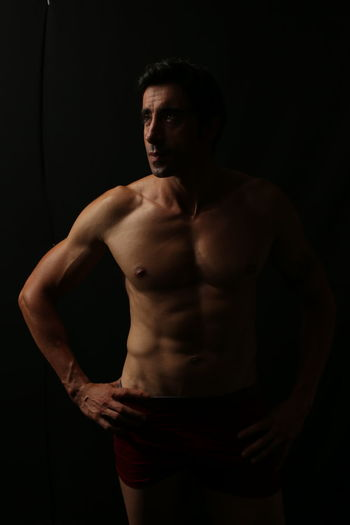 One Person Shirtless Studio Shot Adult Muscular Build Black Background Standing Indoors  Three Quarter Length Hand On Hip Strength Portrait Young Adult Looking At Camera Men Front View Waist Up Males  Abdominal Muscle Chest