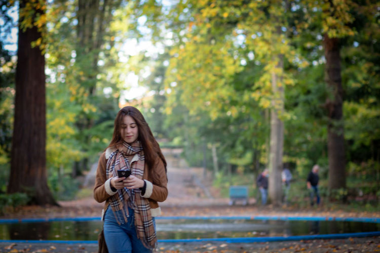 Young woman using phone while standing on land