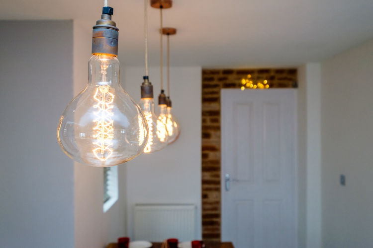 Low angle view of illuminated light bulb hanging at home