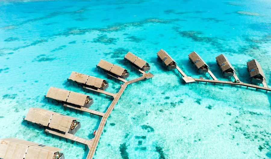 Villas of Paradise. Water Blue High Angle View Day Nature No People Sea Turquoise Colored Swimming Pool Wood - Material Land Sunlight Pool Scenics - Nature Beach Tranquil Scene Outdoors Idyllic Tranquility