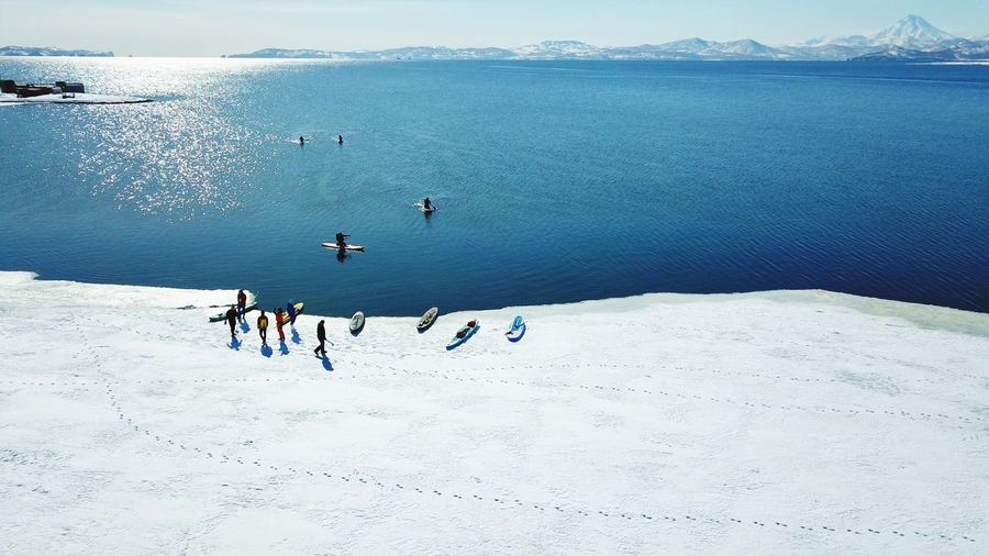 High Angle View Of People Paddleboarding In Sea During Winter