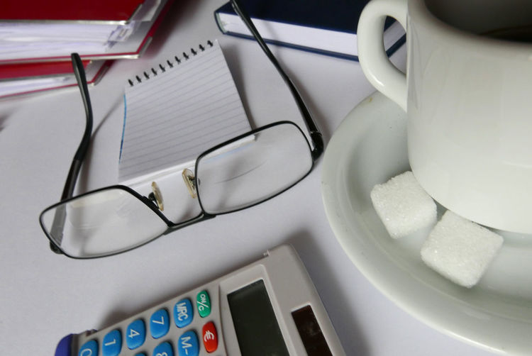 Close-Up Of Coffee Cup And Eyeglasses On Desk At Office