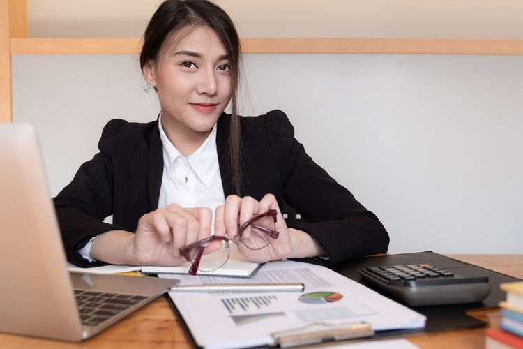 Portrait of businesswoman holding eyeglasses at office