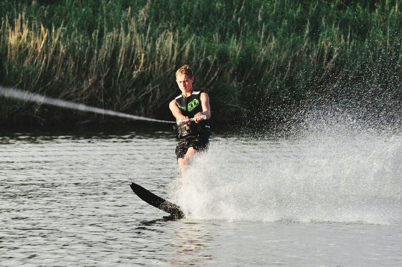 Full length of young woman splashing water