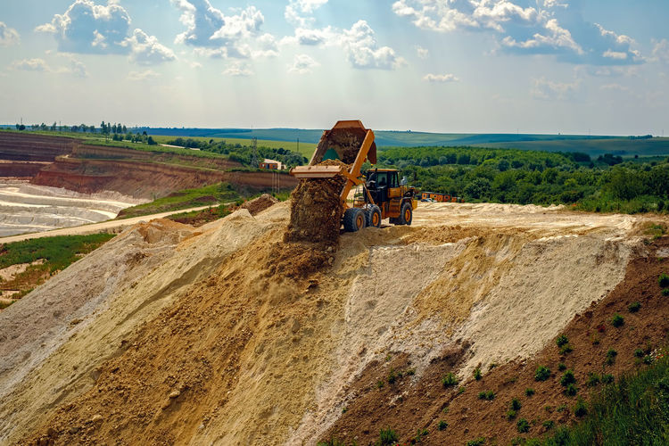 Dump truck unload raw kaolin in kaolin open pit mine Kaolinite Pit Truck Cemetery Cloud - Sky Construction Site Day Dump Truck Dump Trucks Kaolin Landscape Machinery Nature No People Outdoors Pit Mining Raw Kaolin Sky Truck Unload Unloading Working The Great Outdoors - 2018 EyeEm Awards