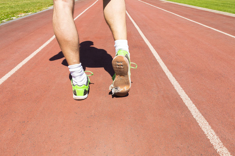 Low section of athlete running with torn shoes on track