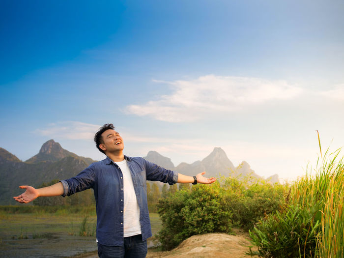 Mountain One Person Standing Beauty In Nature Sky Real People Lifestyles Scenics - Nature Leisure Activity Casual Clothing Non-urban Scene Mountain Range Human Arm Nature Young Adult Front View Tranquility Young Men Tranquil Scene Limb Arms Raised Outdoors