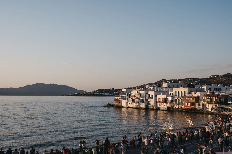 People watching sunset over the old houses in little venice, hora-mykonos town , mykonos, greece.