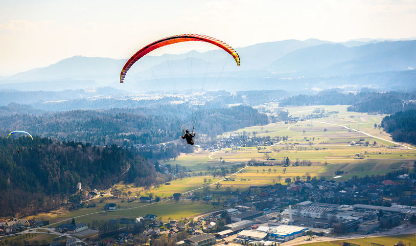 Person paragliding over village
