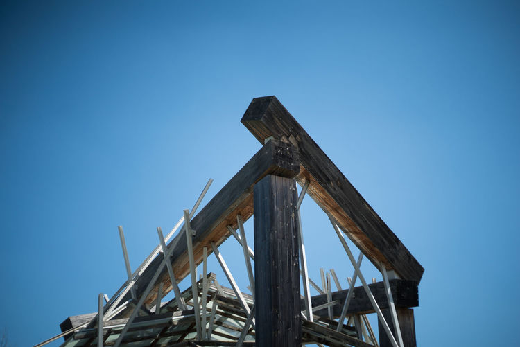 Low angle view of old metallic structure against clear blue sky