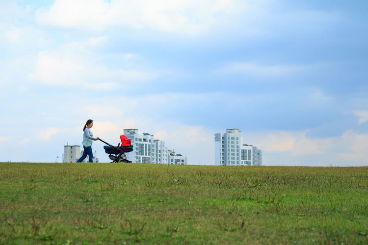 Woman With Baby Stroller Walking On Field Against Sky