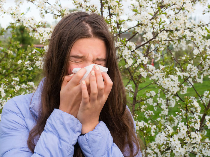 Allergy One Person Plant Flower Real People Young Adult Facial Tissue Lifestyles Cold And Flu Eyes Closed  Flowering Plant Women Human Nose Young Women Nature Front View Illness Beauty In Nature Springtime Fragility Hairstyle