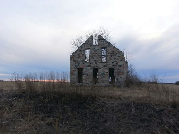 Abandoned house on field against cloudy sky