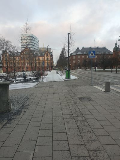 Cobblestone street amidst buildings in city during winter