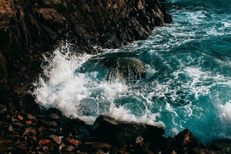 High angle view of sea splashing on rocks