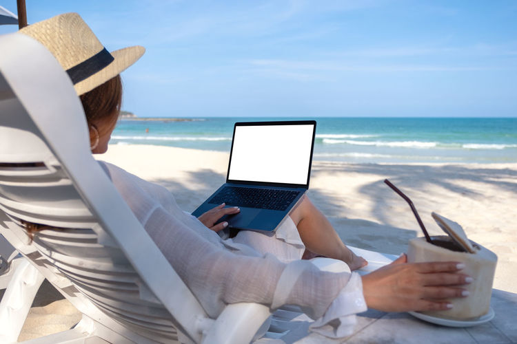 Mockup image of a woman holding and using laptop computer with blank desktop screen while laying down on beach chair and drinking coconut juice on the beach Space Shoulder Sea Screen Sand Relax People Over Online  Notebook Nature Mockup Mock Message Look Lifestyle Laying Laptop Internet Holiday Holding Hand Girl Female Empty Down Display Device Desktop Copyspace Copy Connection Computer Communication Chair Blank Black Beach Background