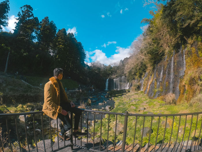 Man looking away while sitting on railing against trees